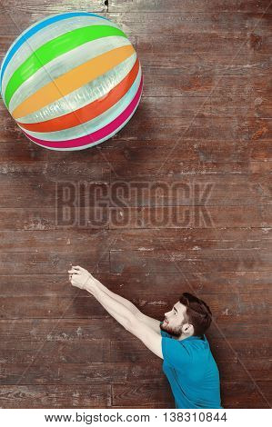 Top view photo of handsome young man on wooden floor. Man with colorful beachball