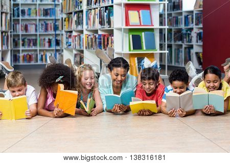 Happy teacher with students reading books while lying down in library