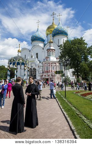 SERGIEV POSAD, RUSSIA - JULY, 10, 2016: Tourists and parishioners around the bell tower. Holy Trinity-St. Sergiev Posad. Moscow region