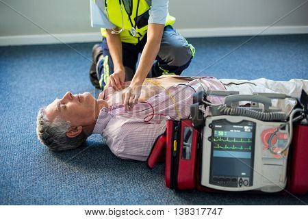 Paramedic using an external defibrillator on an unconscious patient lying on carpet