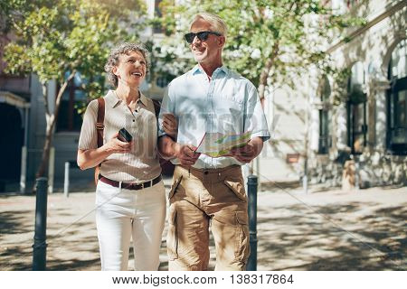 Senior Couple With A Map Walking In The Town.