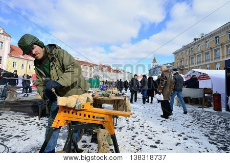 VILNIUS, LITHUANIA - MARCH 2: Unidentified people carve wood sculpture in annual traditional crafts fair - Kaziuko fair on Mar 2, 2013 in Vilnius, Lithuania