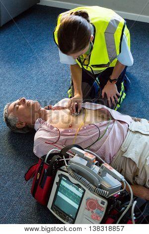 Paramedic examining a patient during cardiopulmonary resuscitation in hospital
