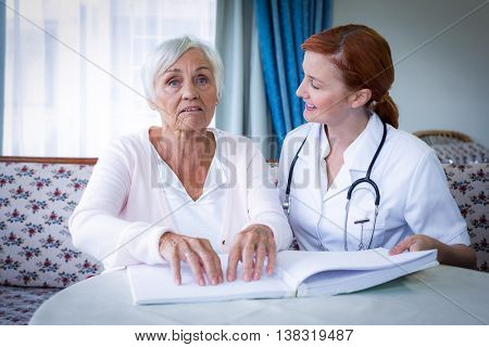Female doctor helping a blind patient in reading the braille book at home