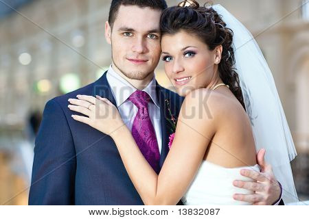 Portrait of Young beautiful wedding couple indoors . poster