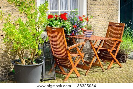 Two wooden chairs and a small tabel before the historic facades of the Begijnhof in the Dutch city of Breda.