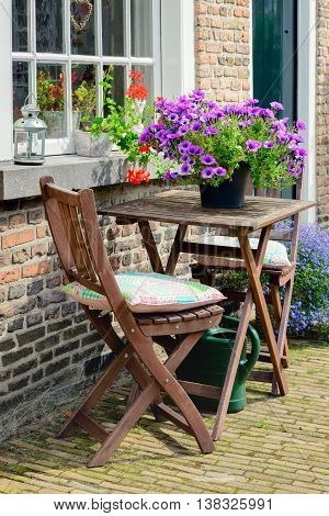 Two small wooden chairs and a table before a historic facade in the Begijnhof in the Dutch city of Breda.