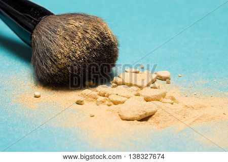 Close-up of crushed mineral shimmer powder golden color with makeup brush on blue background. Very shallow depth of field, focus on powdery brush tip