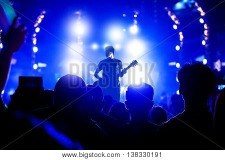 Singer singing on concert stage with ray of illuminated, Singer and guitar on stage