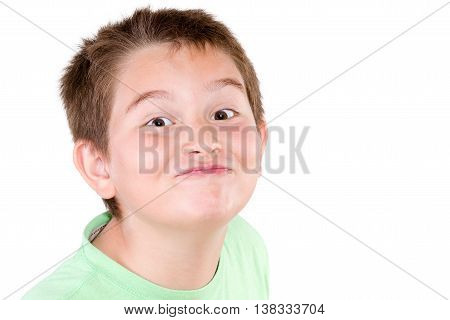 Playful mischievous young boy pulling a cute funny face at the camera with a jaunty look head shot isolated on white
