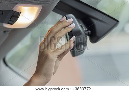 the girl in the cabin of the car  adjusts the rear view mirror
