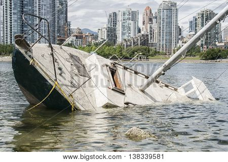 Sinking sailboat abandoned on the shore of a city
