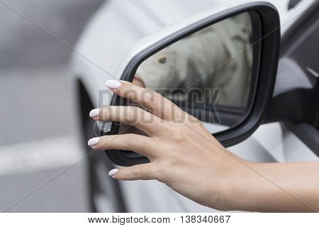 girl with beautiful manicure in car regulates  rearview mirror