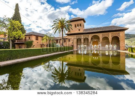 El Partal. A large central pond faces the arched portico behind which stands the Tower of the Ladies, inside the Alhambra of Granada, a World Heritage Site in Andalusia, Spain