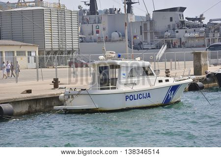 Zelenika town, Montenegro - June 18, 2016: Police boat with military ship on the background ancored in port of Zelenika town.
