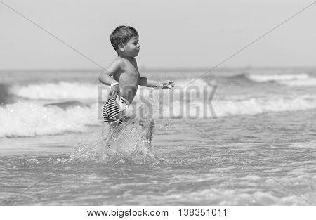 little boy child running through the sea on the beach. joy of life on holiday