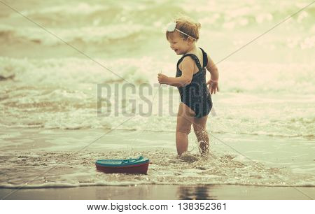 little baby girl laughing on the beach in the water. shu's playing with a toy boat. she's wearing an adorable flower swimsuit. retro style