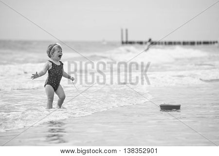 little baby girl laughing on the beach in the water. shu's playing with a toy boat. she's wearing an adorable flower swimsuit. in black and white