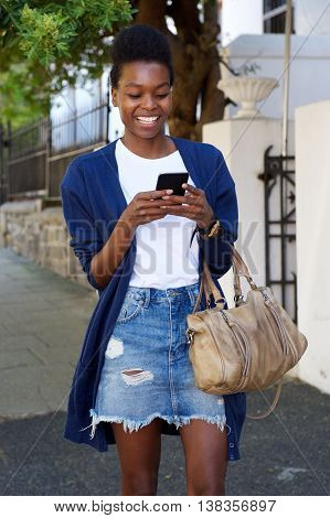 Happy African Woman Using Mobile Phone On The Street