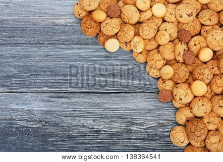 Cookies background. Sweet chocolate chips biscuits heap at blue rustic wood background with copy space. Oatmeal, chocolated drops and other sweets. Fattening dessert for tea on wooden table top view