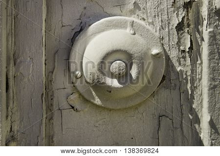 An old style door bell with the advantage of light to show its shape and despair of peeling paint.