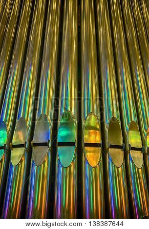 The pipes on a full pipe organ glow with yellow brass and bright colorful reflections from a set of stained glass windows.