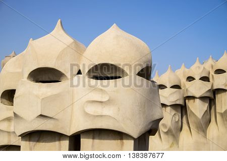 BARCELONA, SPAIN - APRIL 20, 2015: A series of chimneys on the roof of Casa Mila in Barcelona resemble soldiers in helmets. The building was designed by Antoni Gaudi.