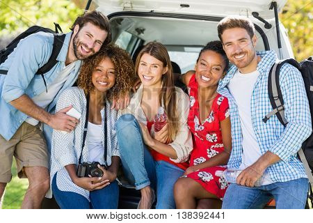 Portrait of friends on trip sitting in trunk of car on a sunny day