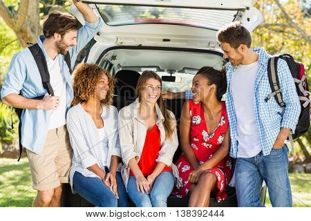 Group of friends on trip sitting in trunk of car on a sunny day
