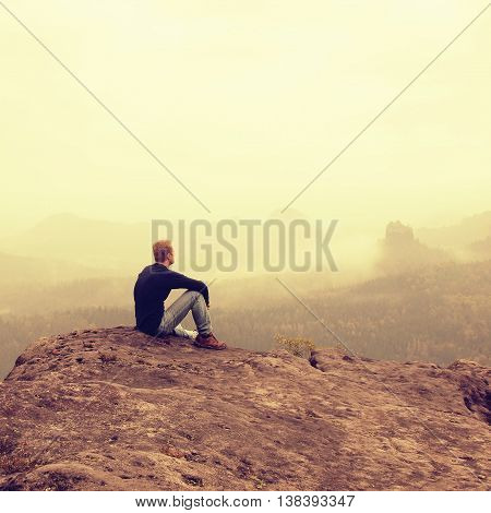 Tourist sit on peak of sandstone rock and watching into colorful mist and fog in morning valley. Sad man. Man sit. Man in jeans.Fall mountain mist. Mist in valleys. Man hand.Sad tourist sit in mist.