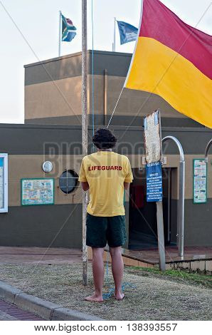 DURBAN SOUTH AFRICA - JULY 13 2016: Lifeguard raising the flag at the Bronze Beach surf rescue station in Umhlanga Rocks