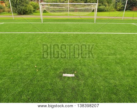 Football playground view of artificial grass field, gate at the end. Detail of a corner in a soccer field. Plastic grass and finely ground black rubber.