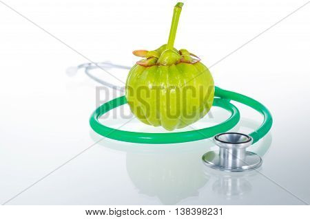 Close Up Garcinia Cambogia And Stethoscope With Reflection On White Background.