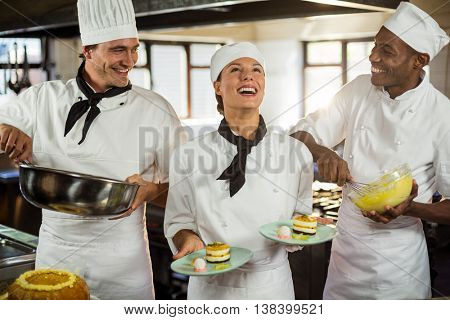 Chefs preparing a dessert in commercial kitchen