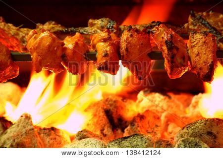 Chicken Tikka on spit cooked over charcoal barbecue