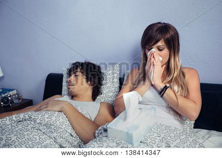Sick woman sneezing and covering nose with tissue sitting on bed side to young man sleeping. Sickness and healthcare concept.