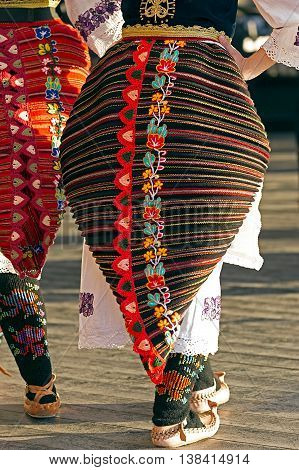 Young girls from Serbia in traditional specific costumes at a folk dance festival.