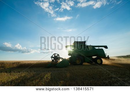 modern combine harvester working on a wheat crop at sunset