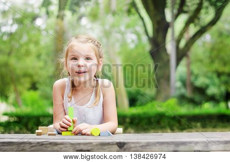 Beautiful and cheerful girl in the park played with l wooden building blocks.