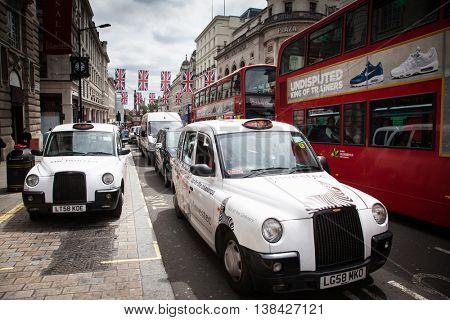 London, England - JULY 28, 2016: Typical black London cab in central London with United kingdom flags in the background