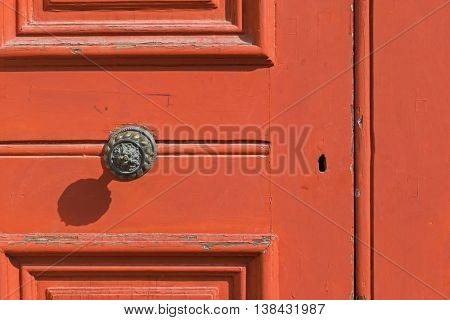 Closeup background of red wooden door with keyhole, brass doorknob with shadow
