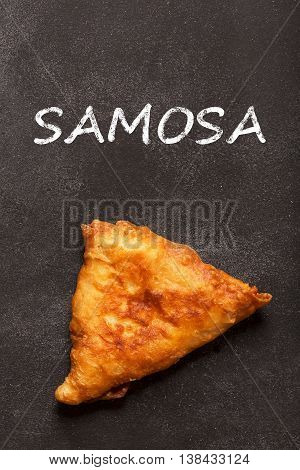 Deep fried indian dish samosa. It could be prepared with meat or vegetables. Image contains name of this food