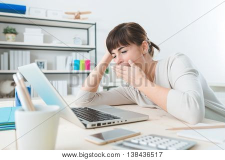 Sleepy young business woman sitting at office desk working with a laptop and yawning poster