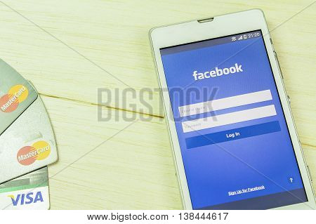 BUNG KAN THAILAND - JANUARY 15 2016: smart phone display facebook app and credit card on wood table facebook logo focused