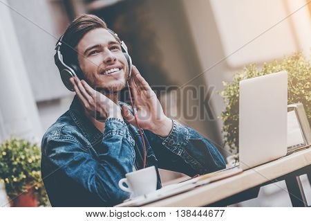 What a great day! Cheerful young man holding hands on headphones while sitting at sidewalk cafe
