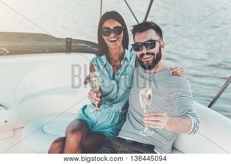 Enjoying great time together. Cheerful young couple holding glasses with champagne and looking at camera while sitting on the board of yacht