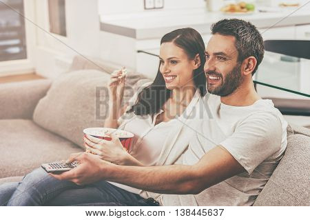 Enjoying favorite show together. Beautiful young loving couple bonding to each other and eating popcorn while sitting on the couch and watching TV