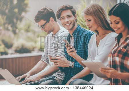 Technologies making lives easier. Group of young people holding different digital devices while man looking at camera and holding mobile phone