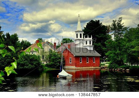 Harrisville,  New Hampshire - July 12 2013: The quintessential New England village of Harrisville with its brick library white steepled church and an 18th century house seen across Harrisville Pond