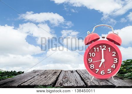 Red alarm clock on a old wooden on blue sky background.